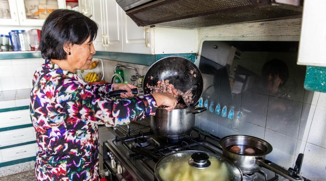 A host mother cooks for Projects Abroad volunteers at their host family accommodation abroad.